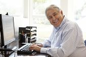 stock photo of hispanic  - Senior Hispanic man working on computer at home - JPG