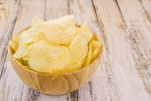 stock photo of potato chips  - Potato chips in wooden bowl on white wooden table background - JPG
