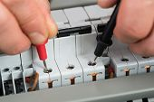 picture of fuse-box  - Close-up Of A Technician Checking Fuse With Multimeter ** Note: Shallow depth of field - JPG