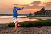 stock photo of tantric  - Female Yoga Model Doing Handstand On Beach at Sunset - JPG