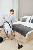foto of housekeeper  - Happy Female Housekeeper Cleaning Floor With Vacuum Cleaner In Hotel Room - JPG