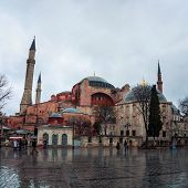 foto of rainy day  - Hagia Sophia at rainy day with blurred people walking by and reflection in the pavement - JPG