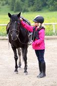stock photo of horse girl  - young girl is standing near black horse - JPG