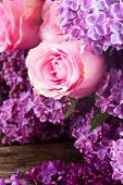 stock photo of purple rose  - Purple Lilac fresh  flowers with pink roses on wooden table close up - JPG