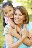 picture of granddaughter  - Hispanic Grandmother And Granddaughter Relaxing In Park - JPG