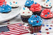 foto of cupcakes  - Chocolate cupcakes decorated in red white and blue and surrounded by stars and flags in celebration of Independence Day - JPG