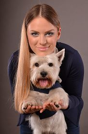 picture of westie  - Cute blonde girl playing with young Westie dog studio shot grey background - JPG