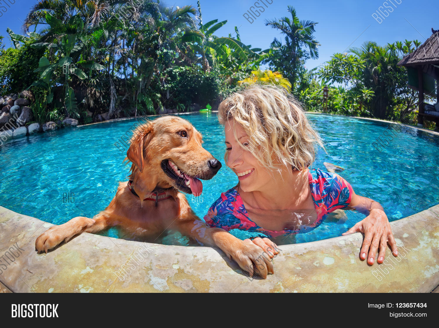 Funny portrait of smiley woman playing with fun and for Garden pool for dogs