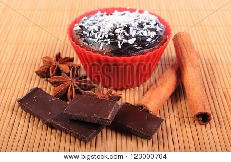 Homemade delicious fresh baked chocolate muffins with desiccated coconut in red silicone cups pieces of chocolate star anise and stick of cinnamon