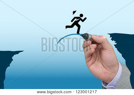 Business hand draws a jump pad to help another business man bridge the gap between two cliffs