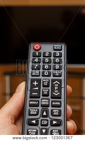 Hand holding infrared remote control for television and TV screen in background