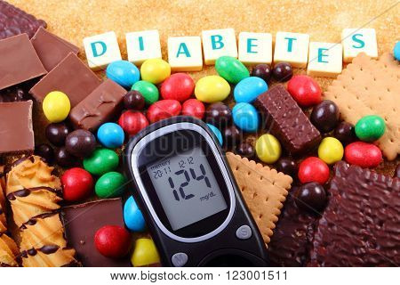 Glucose meter with word diabetes heap of candies cookies and brown cane sugar too many sweets unhealthy food concept of diabetes and reduction of eating sweets