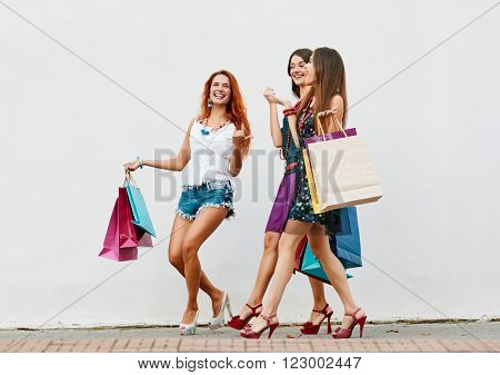 Walking around. Women sisters triplets walking with Shopping Bags On City Street about wall