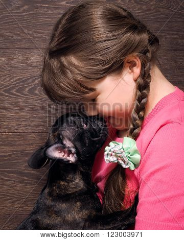 Girl and dog. The girl's face and a large muzzle puppy. Dog black French Bulldog. The relationship of the child and the dog. Concept - trust, love, the contents of the house dogs. dog-child relationship