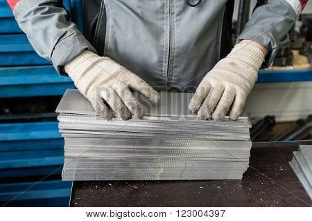 small stack of steel plates on the bench miller, hand in working gloves