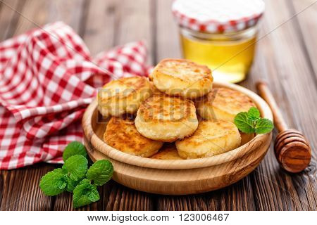 curd fritters with honey and mint on plate