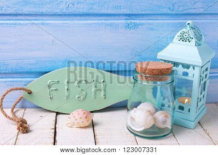 Nauticai theme objects. Decorative fish lantern shells on white wooden background against blue wall. Selective focus. Place for text.