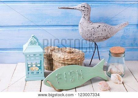 Nauticai theme objects. Decorative fish bird lantern shells on white wooden background against blue wall. Selective focus.
