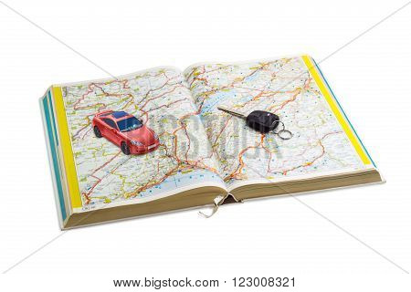 Car key and red toy car on the open road atlas on a light background