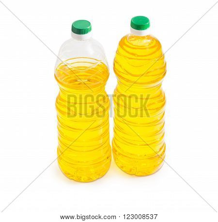 One full and one partially filled plastic bottle of unrefined sunflower oil on a light background