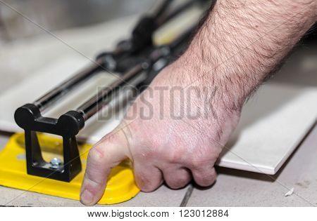 Worker man cuts the ceramic tile closeup