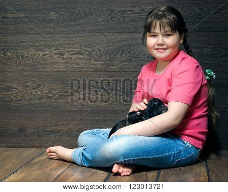Girl with a black dog on the floor near the wooden walls. The dog - french bulldog puppy. Girl in jeans, barefoot. Dog and little mistress. Girl full