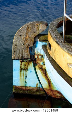 An old and well used wooden rudder on the stern of a boat. The paint is flaking and the rust is coloring the surrounding material.