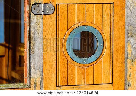 Detail of a small circular window on a wooden boat cabin door. A hinge and part of a bigger window visible. A metal frame surround the glass on the door.