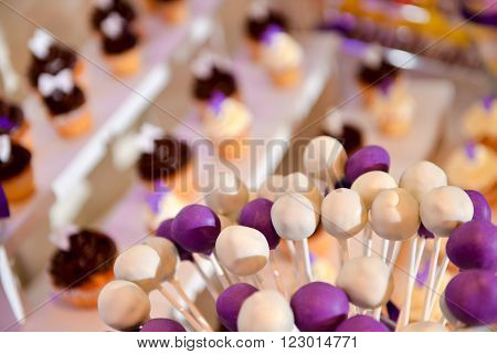 White and mauve lollipops with many cake in background