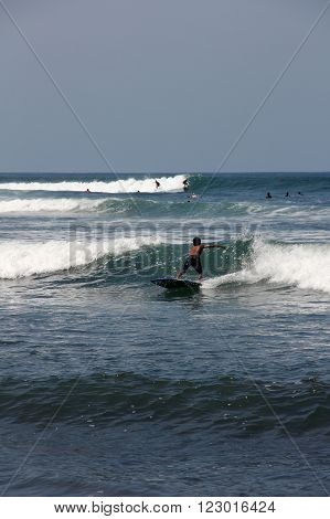 Boy do surfing on waves in Bali island. Some surfers are nearby. Blue sea and white sea foam.