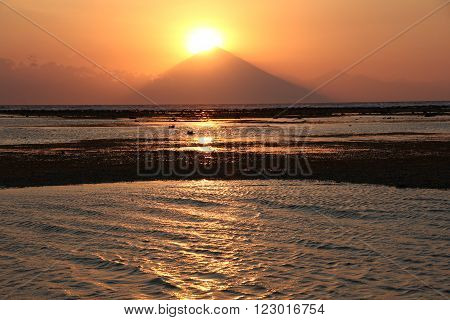 View of orange Sunset over Bali highest volcano Mt. Agung from Gili island. Mountains and ocean.
