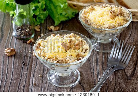 Salad With Chicken, Walnuts And Cheese On A Dark Wooden Table