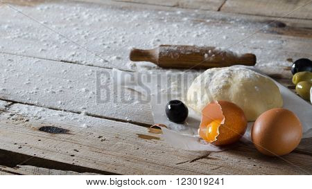 elastic dough sprinkled with flour on parchment paper one whole egg and one broken egg and olives and a rolling pin on a wooden board ** Note: Soft Focus at 100%, best at smaller sizes