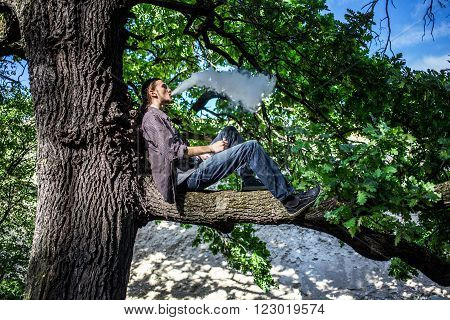 Young man vaping electronic cigarette and sitting on the tree. Daylight summer shot.