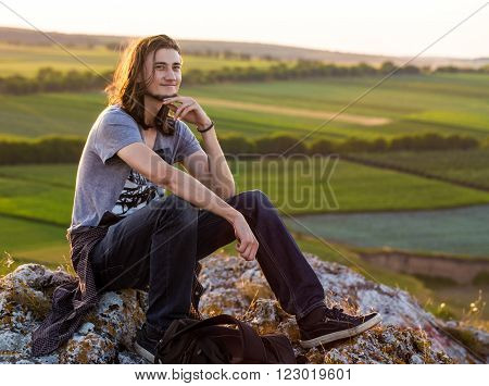 Handsome young longhair man sitting on a rocks against fields and blue background. Sunset shot.