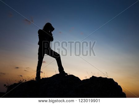Silhouette of young longhair male model making photo shot with dslr camera at blue and yellow sunset.