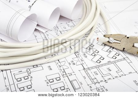 Architecture plan and rolls of blueprints with cabel and pliers. Building concept