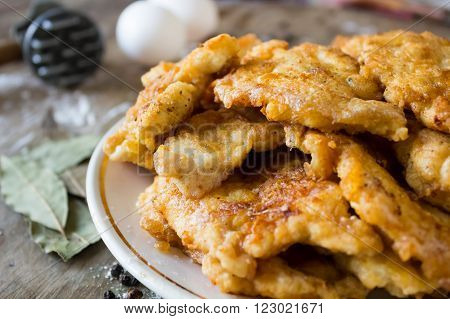 Prepared delicious chicken nuggets with flour eggs next to hammer for beating the meat bay leaf
