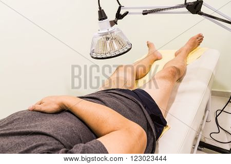 Acupuncture Patient Being Treated With Needles And Infrared Heat Lamp