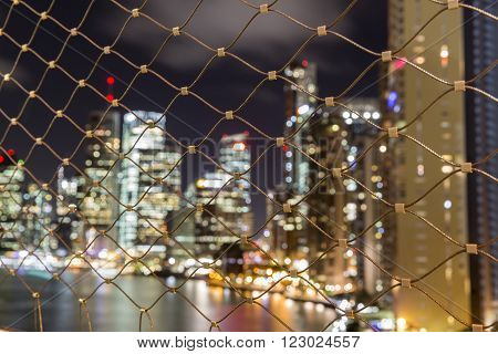 BRISBANE, AUSTRALIA - MARCH 3 2016: Brisbane city by night blurred lights, looking though the Story Bridge suicide mesh prevention barriers.