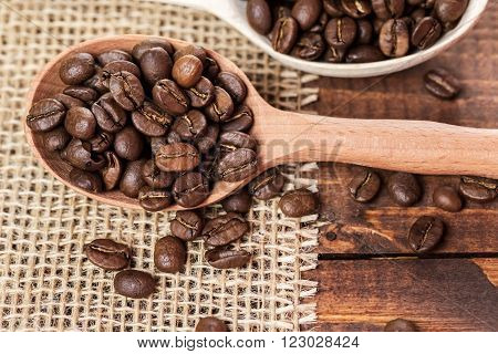whole coffee beans in a wooden spoon and a scattering of coffee beans on burlap and old brown boards with free space for your text