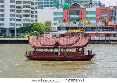 Bangkok, Thailand - Aug 15, 2015: wooden ferry transfer boat with Thai-style roofs and ornate grill work panels crossing the Chao Praya River