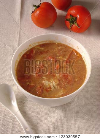 Tomato and scrambled eggs soup in bowl.
