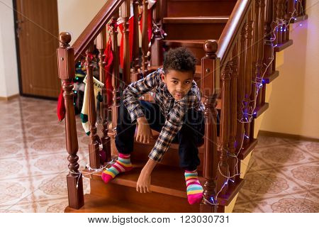 Black kid sitting on staircase. Boy at home during Christmas. Waiting for guests to come. Feeling bored on holiday.