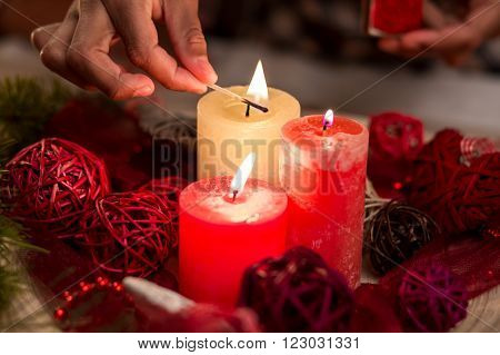Child's hand lighting Christmas candles. Close-up of candles being lit. Candles and red wire balls. Symbolic Christmas decorations.