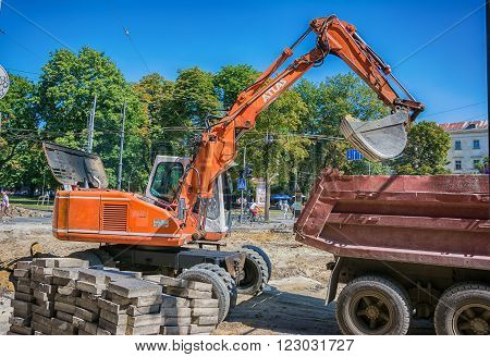 Lviv Ukraine - August 19 2015: Excavator loader machine works at ancient historical center of Lviv