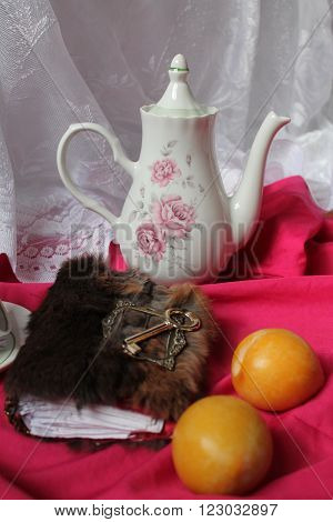 porcelain fragile pot , notebook in fur cover with golden key, two yellow pulp plums nice rest  and coffee time