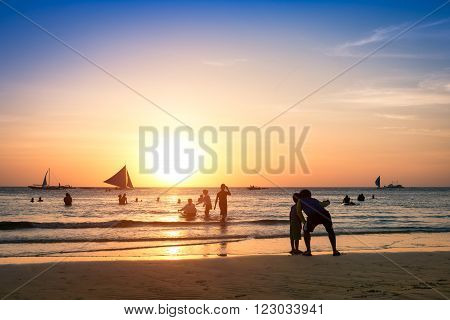 Silhouette of unrecognizable tourists and local people with father and son taking selfie at Boracay beach during sunset - Exclusive travel fun destination in Philippines - Warm enhanced filtered look