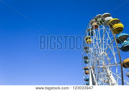 Ferris wheel on the background of clear blue sky. Horizontal shot background