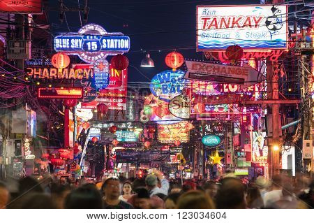 PATTAYA THAILAND - FEBRUARY 18 2016: multicolored neon signs and blurred people on the new Walking Street of the city - The road is closed to the traffic after 6pm and stays crowded until late night